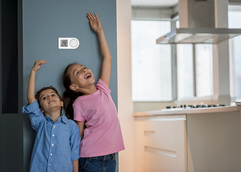 Kids standing under a smart thermostat